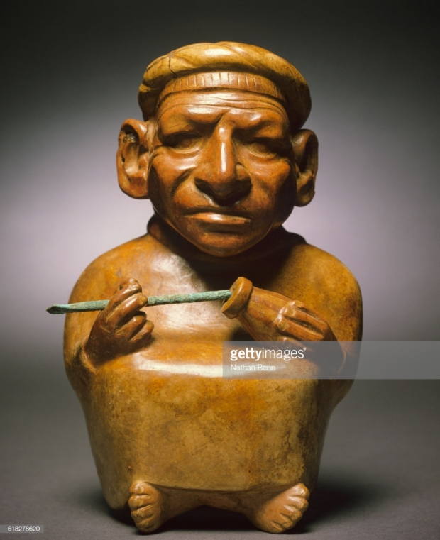 Moche ceramic vessel of a person chewing coca leaves and holding a gourd of lime.